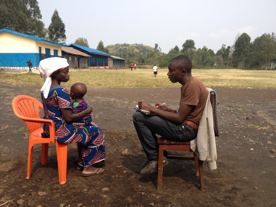 Arsene talking to one of our beneficiaries to learn about her story